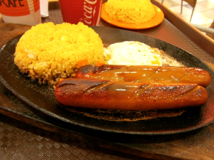 Egg, hotdogs and rice on a sizzling plate