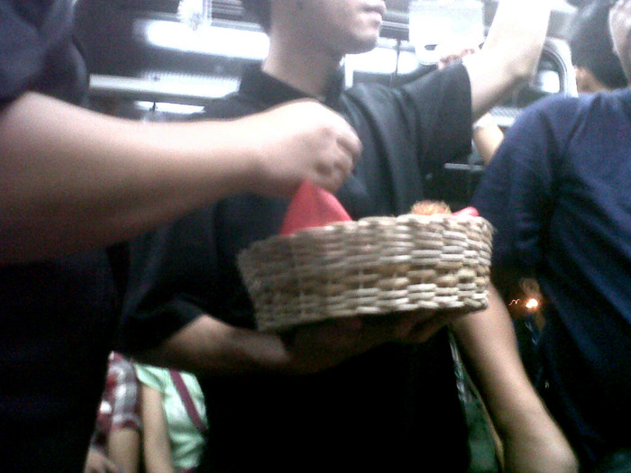 A group of guys eating a basket of rambutan inside the MRT - Philippines
