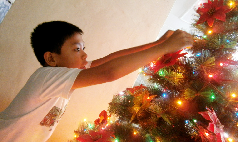 My nephew JB hanging ornaments on our Christmas tree - Christmas in the Philippines