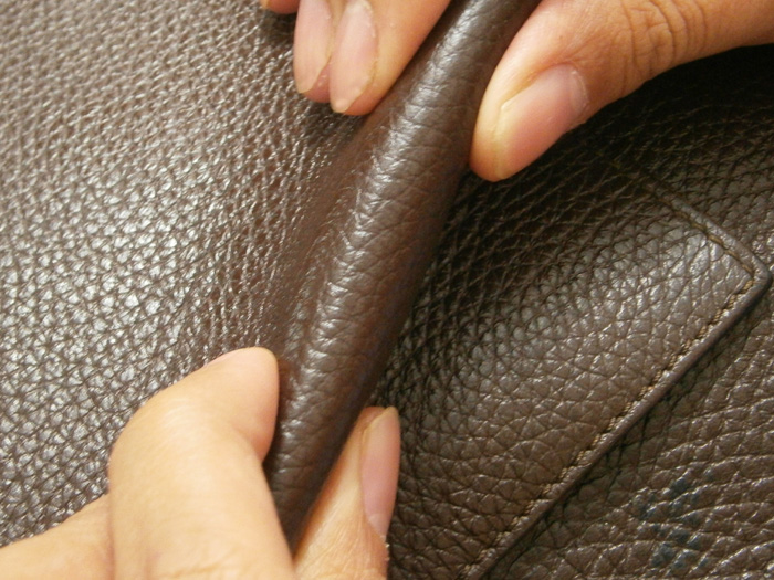 Carefully bending the dent on the leather the other way