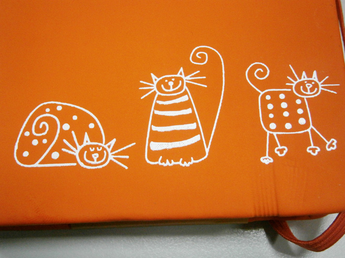 Closer view of the three kitties in this notebook