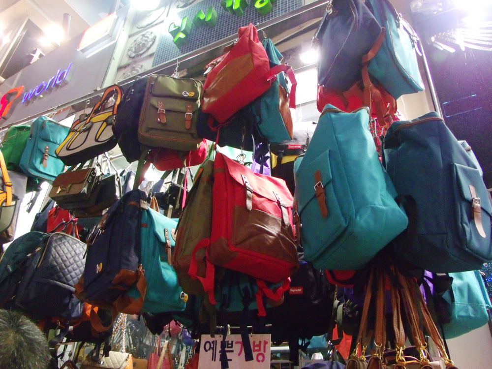 A bunch of canvas backpacks hanging from a shop in Myeongdong, Seoul, South Korea