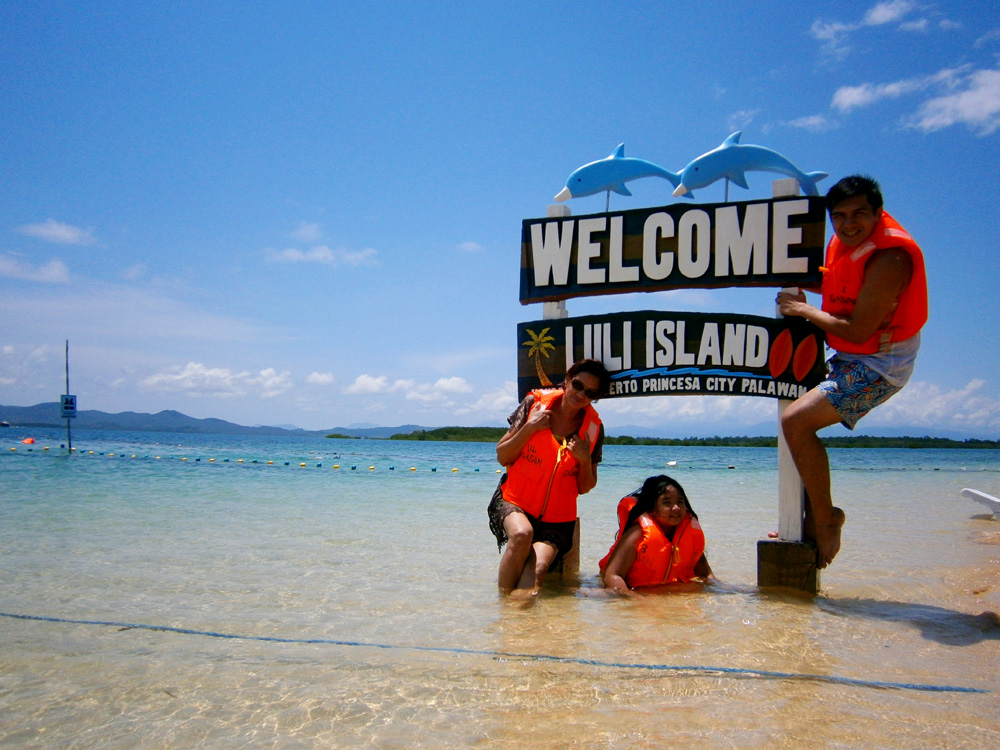 Mon and his family by the Luli Island sign