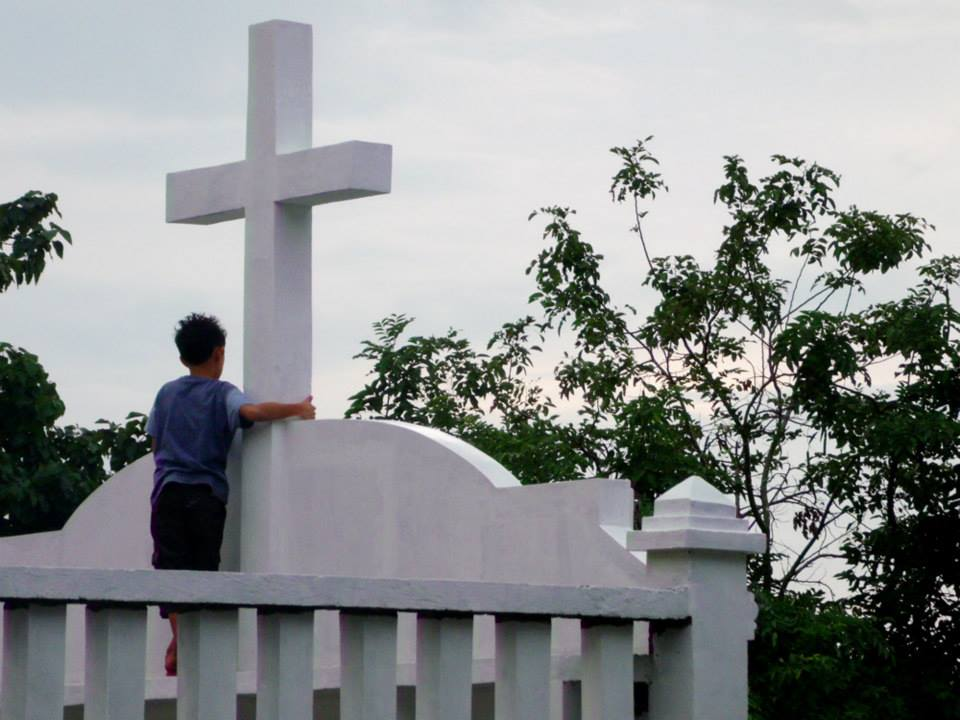 A kid by the cross in a mausoleum in Mabini Cemetery