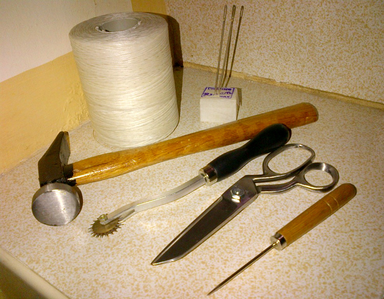 The basic tools - linen thread, paraffin wax, needles, hammer, stitch marker, scissors and awl